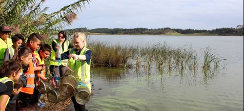 Children looking at fish traps on lake's edge.
